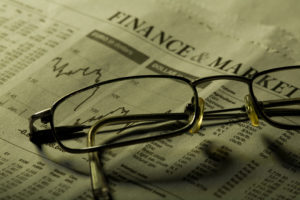 Business sectionin newspaper concept. Focus on glasses under green light