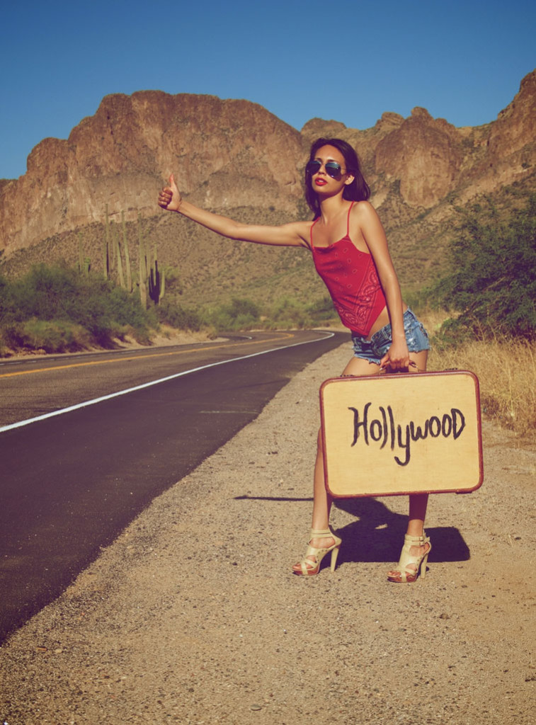 Girl by a road with Hollywood suitcase