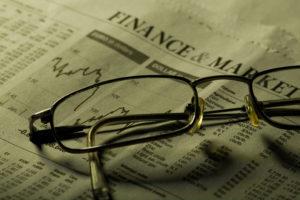 Business sectionin newspaper concept. Focus on glasses under green light