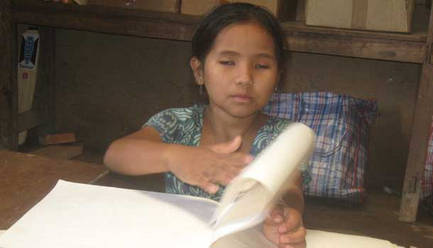 Blind child reading her book