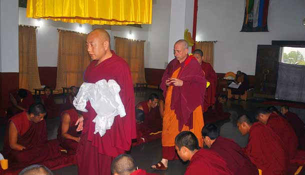 Having made prostrations at the door of the temple, Nicky walks down a central row of monks